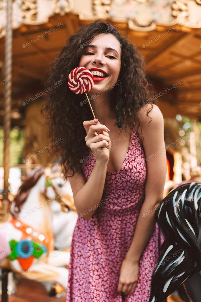 Smiling girl in dress holding lolly pop candy happily looking in camera in amusement park