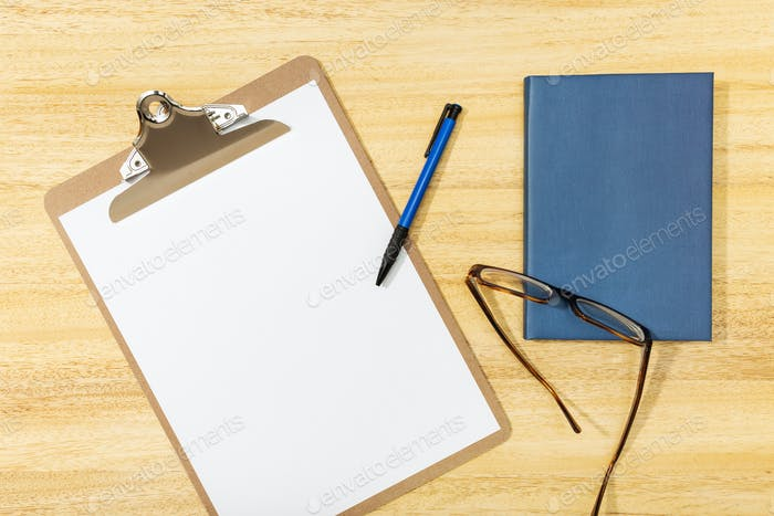 Workspace with blank clip board, pen, glasses and diary on wooden table