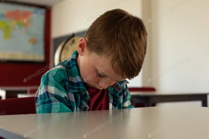Front view of Caucasian boy sleeping at desk in classroom at elementary school