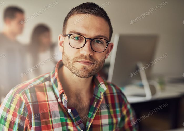 Handsome bearded worker in small office