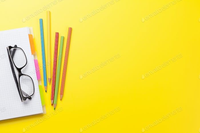 Office yellow backdrop with supplies and glasses