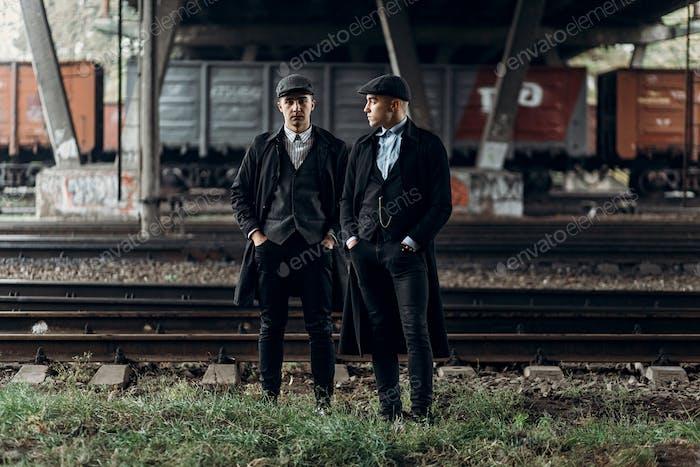 Стильные бандиты мужчины, позируя на фоне железной дороги