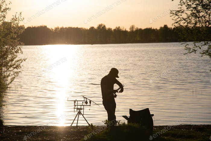 A fisherman silhouette fishing at sunset