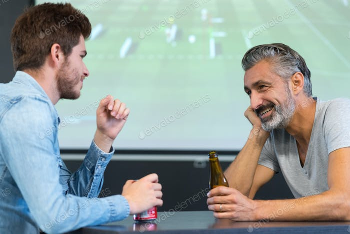 friends watching a football match while drinking beer