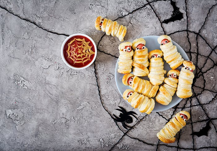Scary sausage mummies in dough with funny eyes on table.