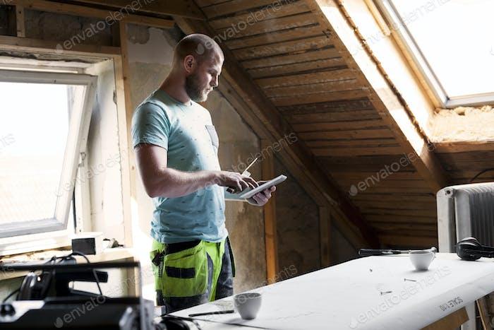 Mann arbeitet an der Renovierung alten Dachboden mit Tablet