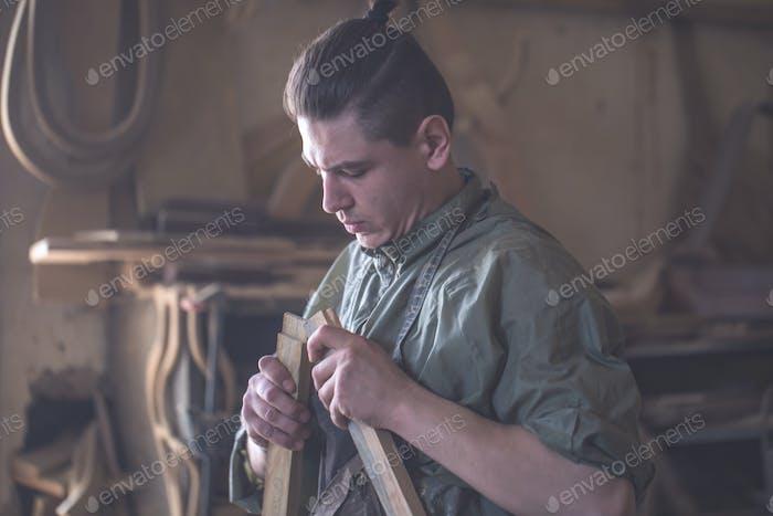Schreiner arbeitet mit einem Holzprodukt, Handwerkzeuge