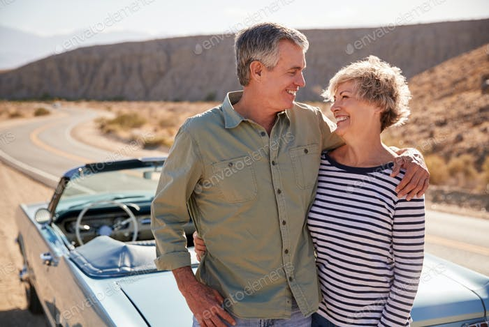 Happy senior couple on road trip standing next to their car