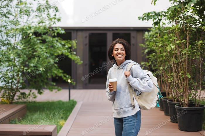 Smiling lady with dark curly hair standing with backpack and cup of coffee to go in hand