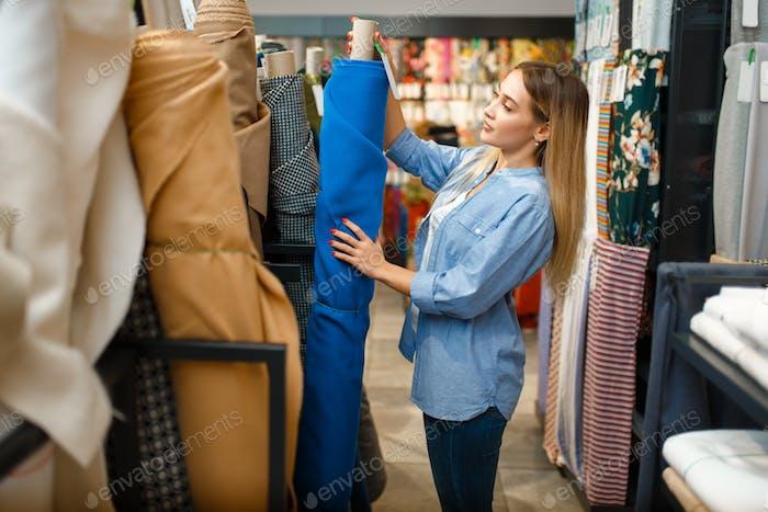 Näherin nimmt Stoffrolle in Textilwerkstatt