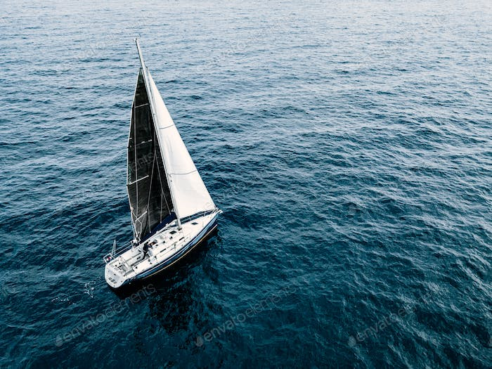 Aerial view of sailing ship yacht with white and black sails at deep open sea.