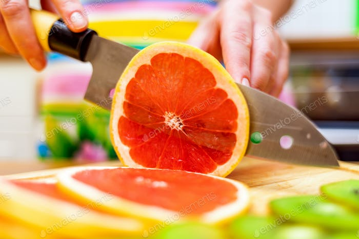 Women's hands Housewives cut with a knife fresh grapefruit on th