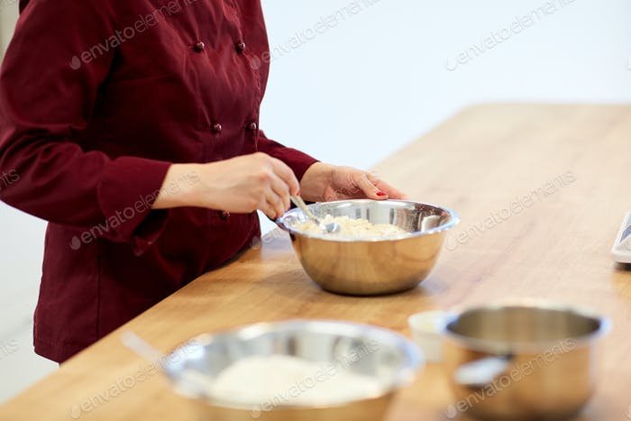chef with flour in bowl making batter or dough