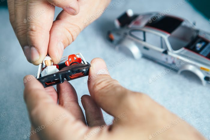 Person plugging driver in slot car