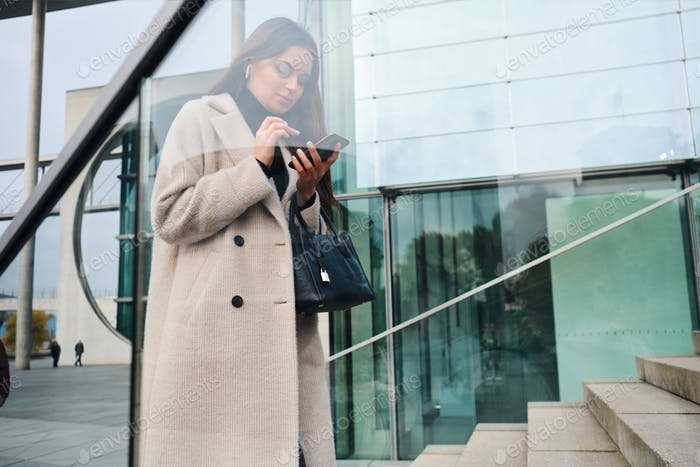 Young businesswoman in coat with handbag confidently using cellphone outdoor