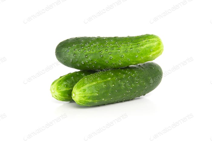 Three fresh cucumbers on a white background.