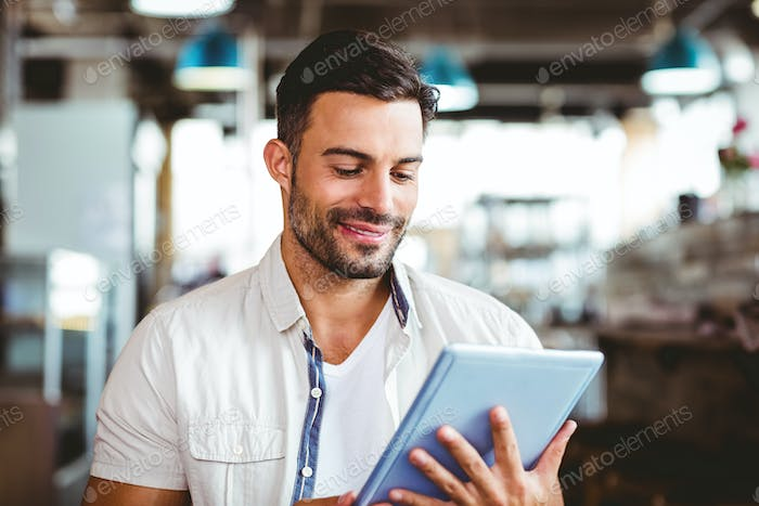 Young man having cup of coffee using tablet at the cafe