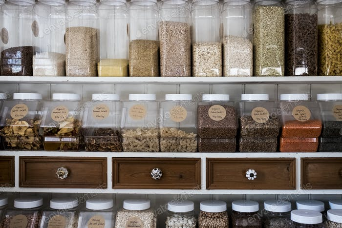 Close up of shelves with a selection of pasta, legumes and grains in glass jars.