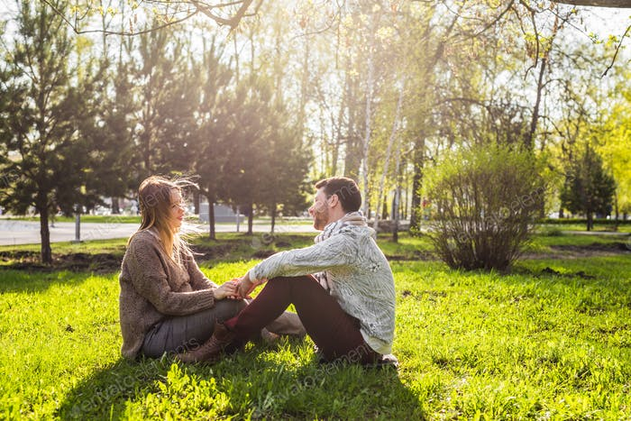 Romantic young couple in love relaxing outdoors in park