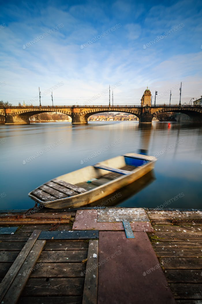 Sunrise view at Vltava river bridge and boat Prague Czech republic.