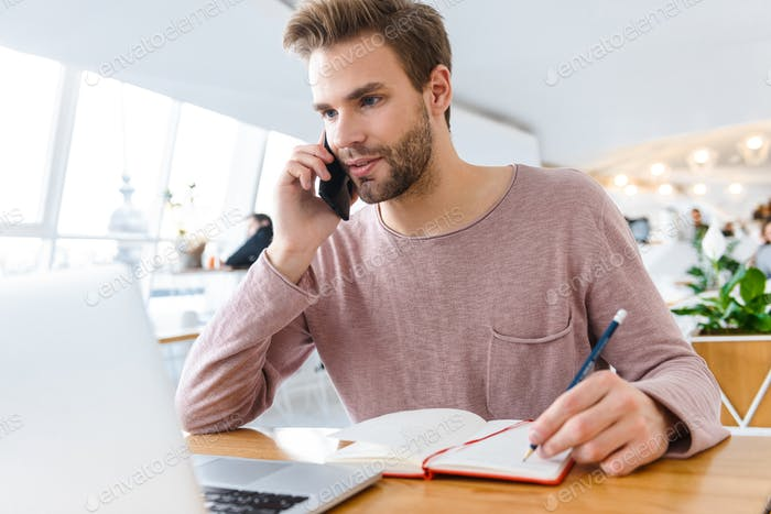 Image of man working on laptop and talking on cellphone in cafe indoors