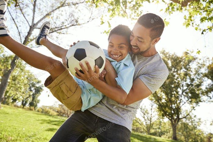Vater und Sohn spielen Fußball in Park zusammen
