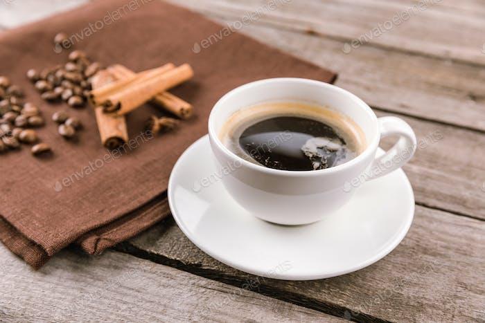 close up view of coffee mug steam and cinnamon sticks