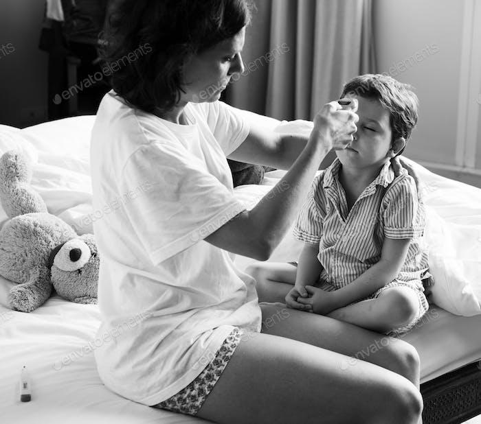 Junge sitzt auf dem Bett und seine Mama Überprüfung Temperatur