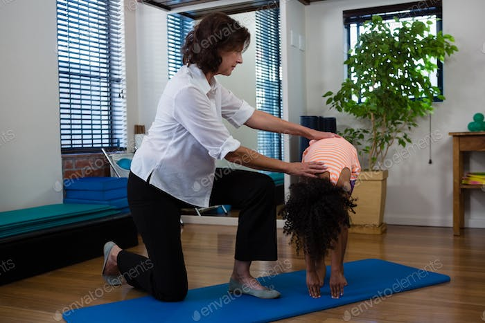 Physiotherapist assisting girl in exercising