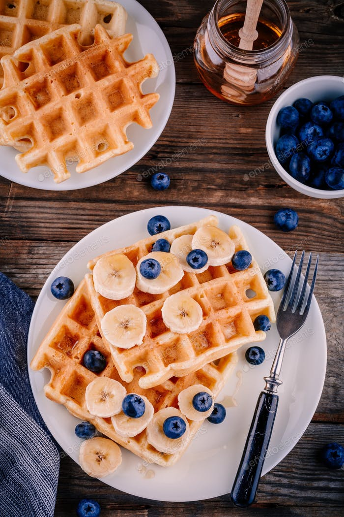 Fresh homemade belgian waffles with blueberries and banana for breakfast