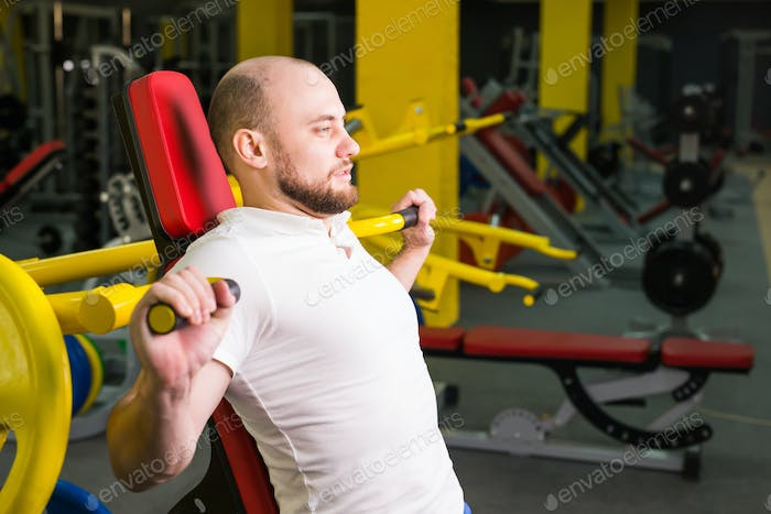 Athletic male doing workouts with power exercise machine in a gym club.