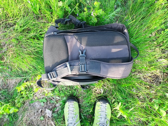 Tourist sneakers and backpack against background of green grass