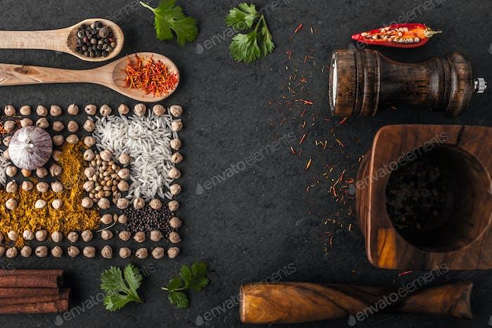 Zusammensetzung von Kichererbsen und Gewürz mit Holzgeschirr auf dem dunklen Tisch