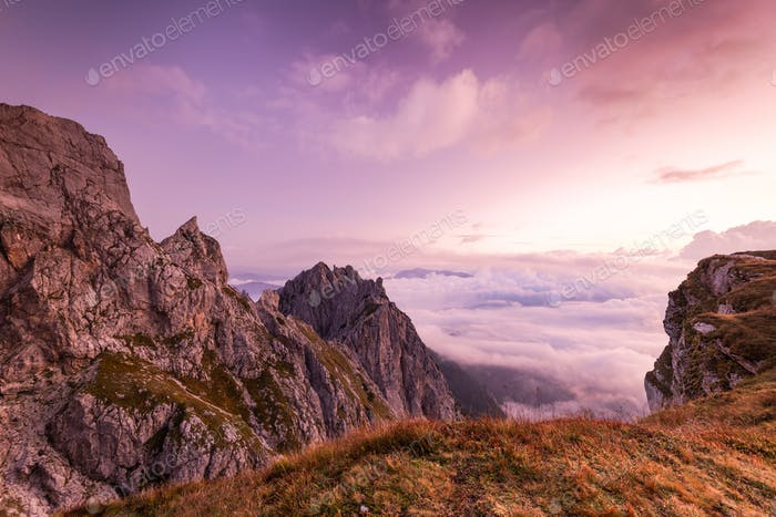 Breathtaking Sunrise at Mountains Peaks above Clouds. Pink Color