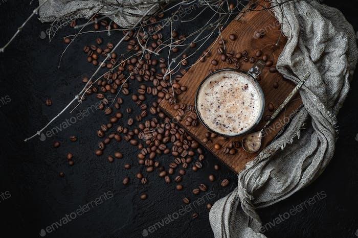 Kaffee mit Milchschaum auf einem dunklen Hintergrund. Low-Key-Fotografie.
