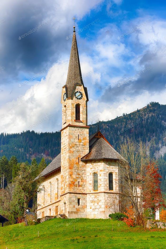 Berge über dem Dorf Gosau mit katholischer Kirche unter Sonnenlicht.