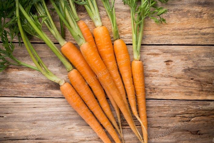 Karotten mehr auf einem hölzernen Hintergrund. Studio-Fotografie.