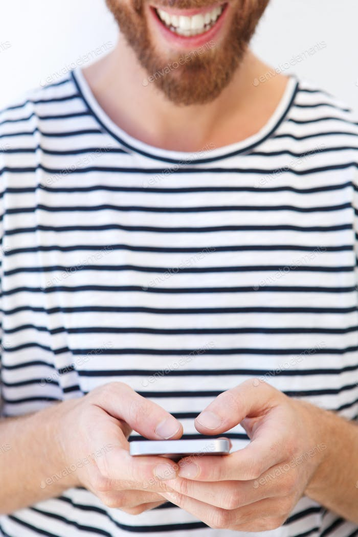 smiling man in striped shirt holding mobile phone