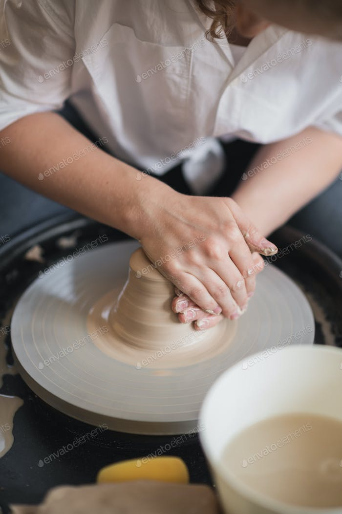 Potter makes the clay product with pottery modeling tools on the potter's wheel