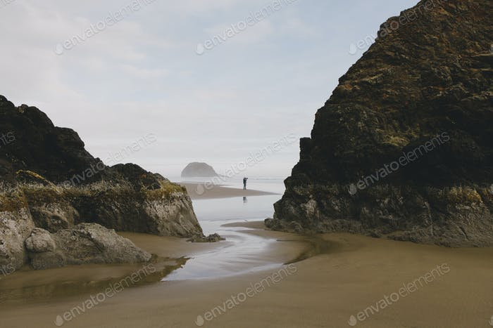 Man taking photographs on a beach at low tide, Arcadia Beach State Park, Oregon