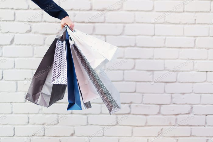 Sale, discount, black friday concept. Man with bunch of shopping bags. Copy space. Shopping mall and