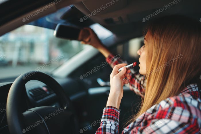Woman driver paints her lips with lipstick in car