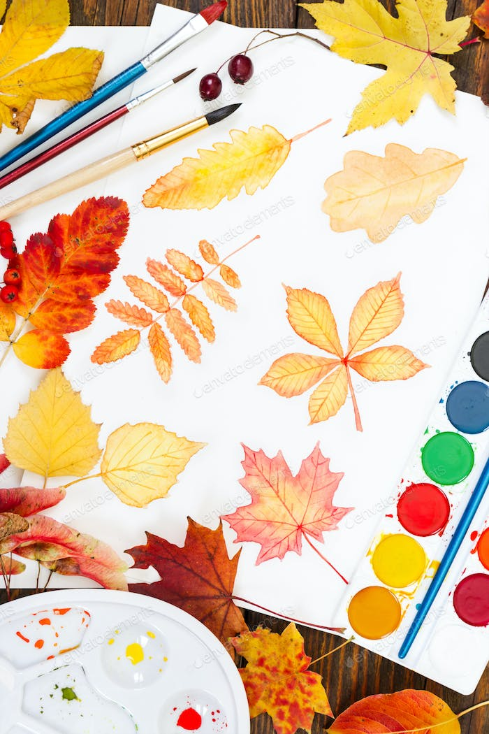 Watercolor painting with autumn leaves, paint, brushes, palette