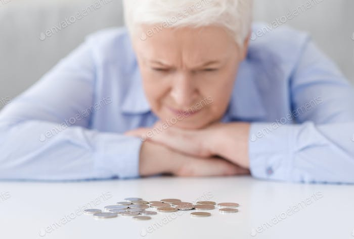 Elderly Poverty. Depressed senior woman looking at last coins lying at table