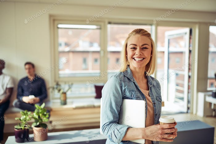 Smiling young businesswoman standing in an office during her break