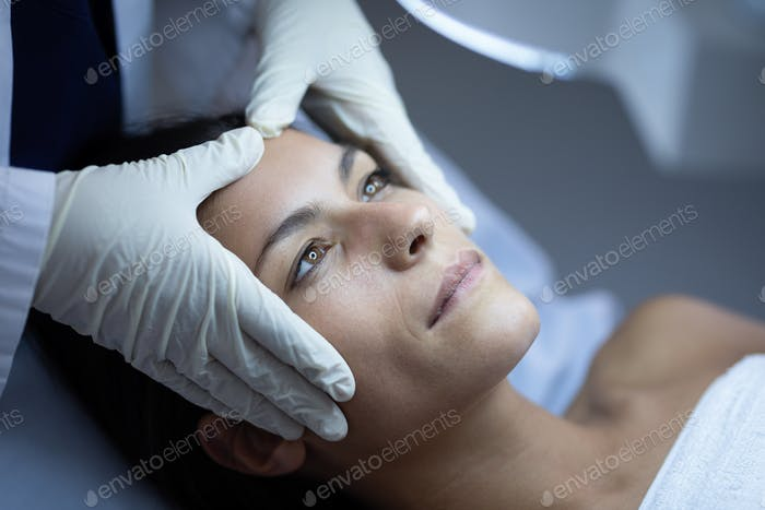 Side view of a female surgeon examining her Caucasian patient during plastic surgery in clinic