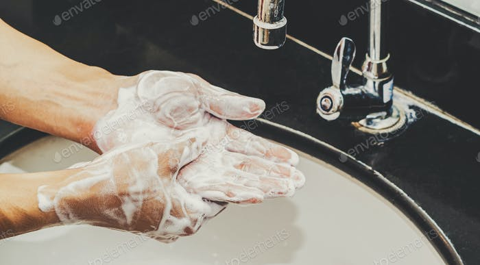 Closeup hands washing with Chrome faucet and soap for Coronavirus pandemic prevention in bathroom
