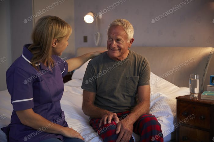Nurse Talking With Senior Man In Bedroom On Home Visit