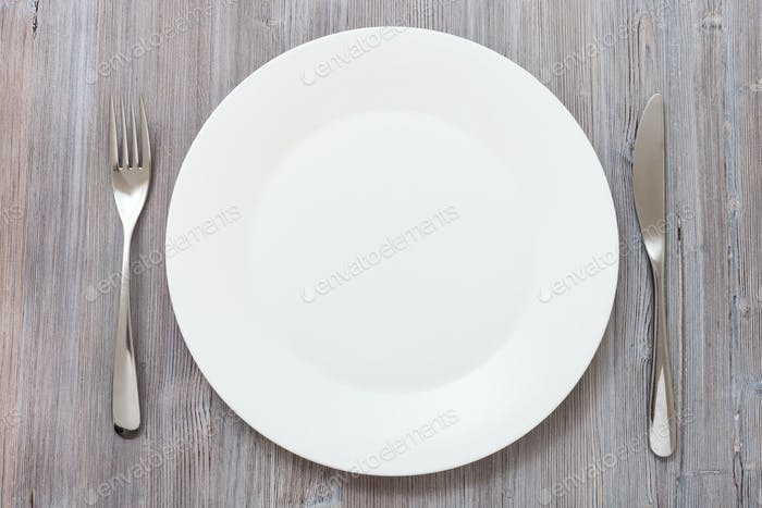 top view of white plate, knife, spoon on gray