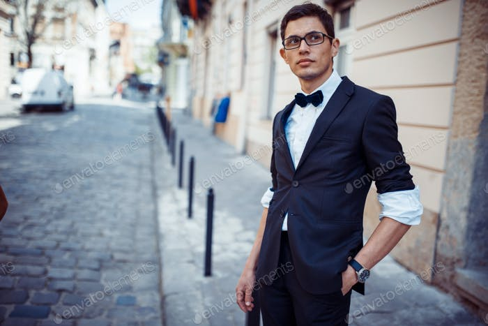 Portrait of fashionable well dressed man posing outdoors looking away